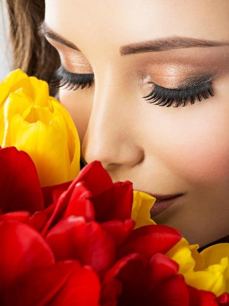 꽃을 가진 젊은 여자의 근접 촬영 아름다움 얼굴. 빨간색과 노란색 튤립과 매력적인 모델 무료 사진