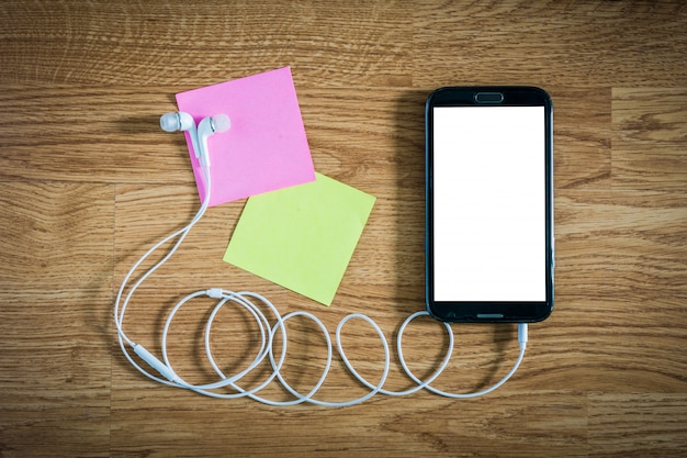 Closeup of black smartphone with white screen with headphones, sticky notes on wooden surface Premium Photo