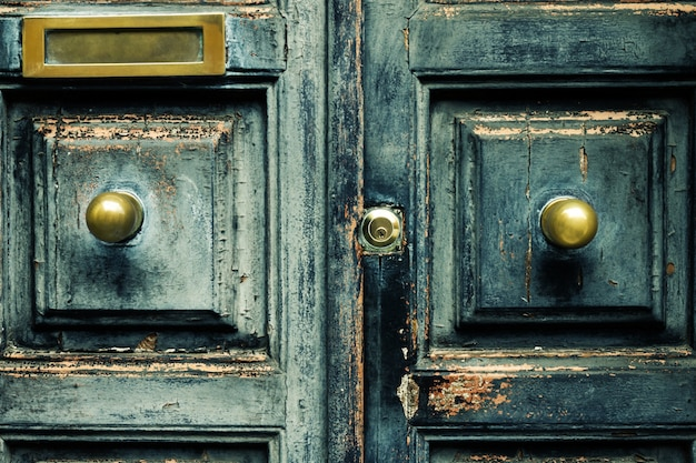 Closeup of blue turquoise old textured antique door with gold bronze door handle and keyhole. Free Photo
