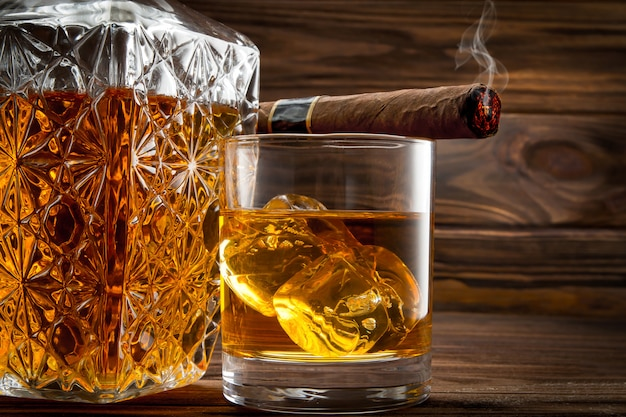 Closeup of bottle, glass with whiskey and smoldering cigar Premium Photo