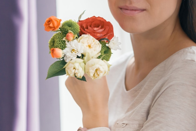 Closeup of bouquet flowers in hand young smiling woman Premium Photo