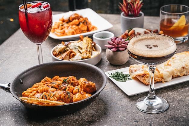 Primo piano di ciotole di pasta cotta con insalate, deliziosi cocktail e verdure fritte sul tavolo Foto Gratuite
