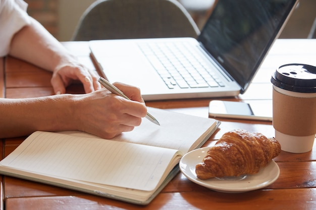 Closeup of breakfast table with female hands putting down information to the daily planner Free Photo