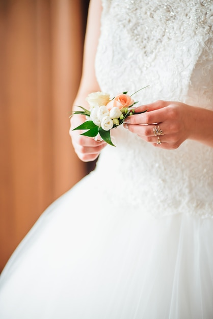 Closeup of a bride holding wedding boutonniere in the hands. in the morning, wedding day Premium Photo