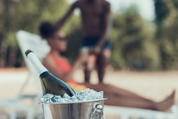 Closeup of bucket with ice and champagne on foreground Premium Photo