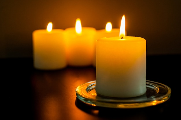 Closeup to burning candles in darkness Premium Photo