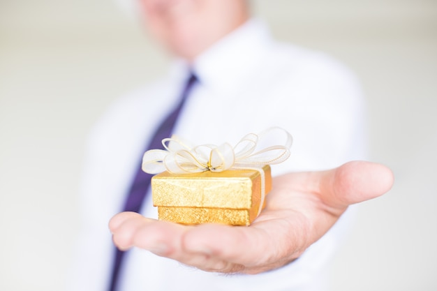 Primo piano di uomo d'affari dando piccola confezione regalo Foto Gratuite