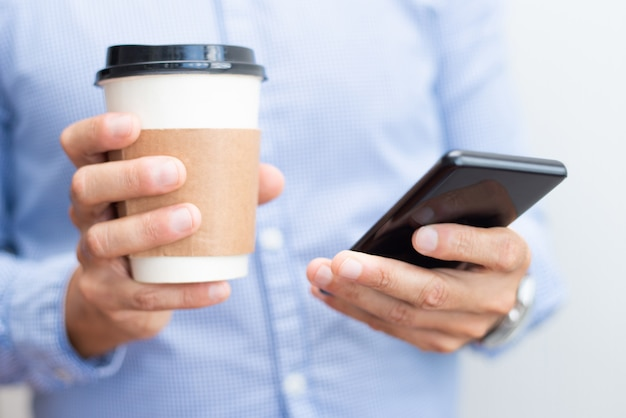 Closeup of business man holding smartphone and drink Free Photo
