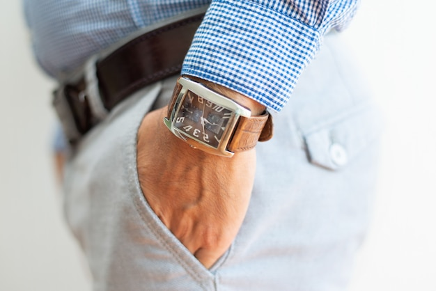 Closeup of business man keeping hand in trousers pocket Free Photo