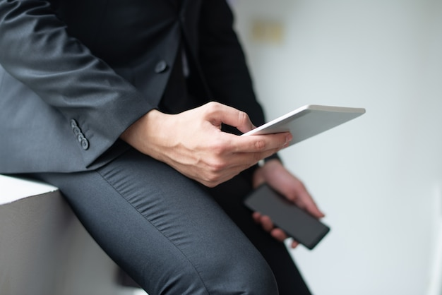 Closeup of business man using gadgets and leaning on sill Free Photo