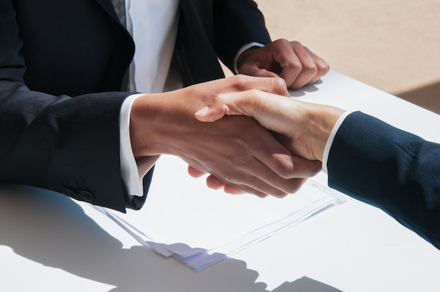 Closeup of business people shaking hands outdoors Free Photo