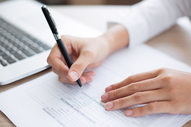 Closeup of business person completing form Free Photo