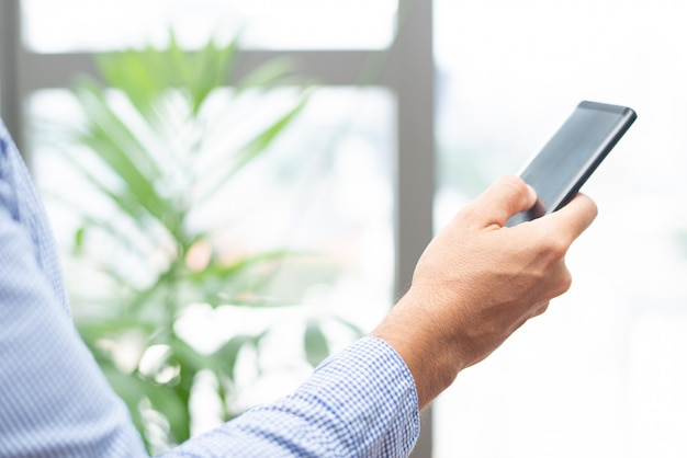 Closeup of business person tapping on smartphone screen Free Photo