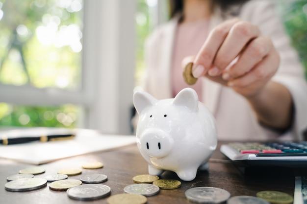 Closeup of business woman hand putting money coin into piggy bank for saving money. saving money and financial concept Premium Photo
