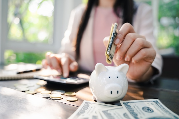 Closeup of business woman hand putting money into piggy bank for saving money. saving money and financial concept Premium Photo