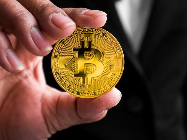 Closeup businesswoman showing gold bitcoin. Premium Photo