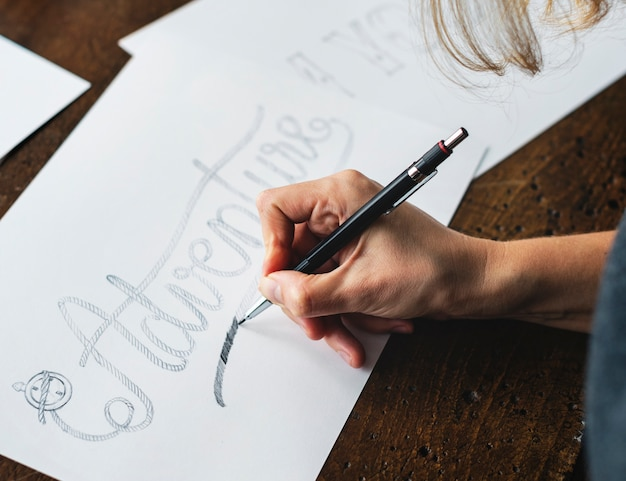 Closeup of a calligrapher working on a project Free Photo