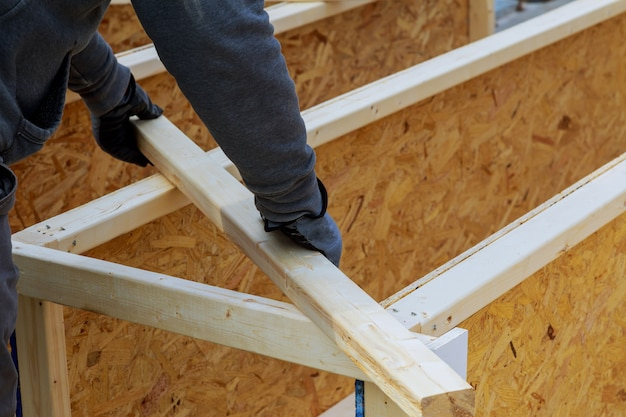 Closeup of a carpenter's hands on a construction site. focus on drill and hand. Premium Photo