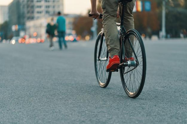 Closeup of casual man legs riding classic bike on city road Free Photo