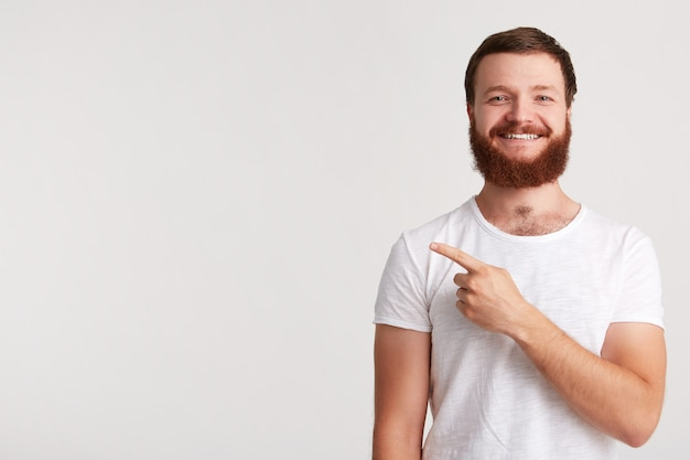 Closeup of cheeful confident young man hipster with beard wears t shirt feels happy and points to the side with finger isolated over white wall Free Photo