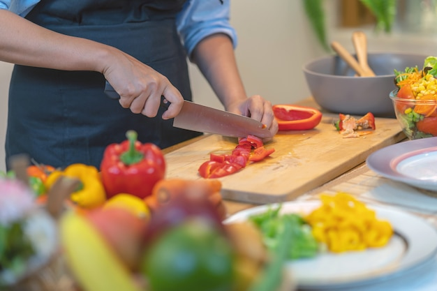 Premium Photo Closeup Chef Hand Cutting The Bell Pepper On The Chopping Board In Modern Kitchen
