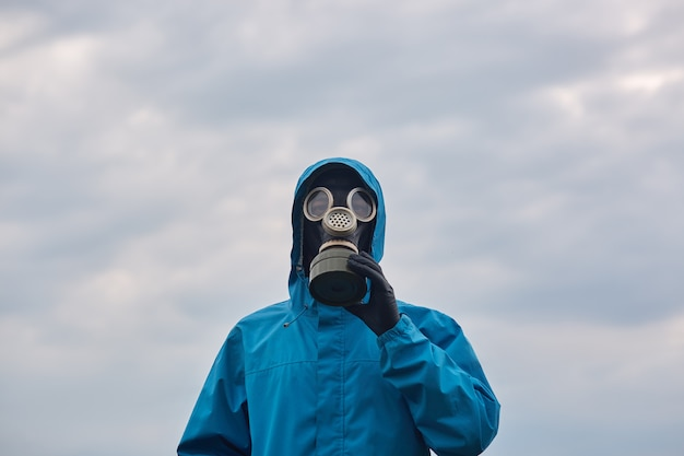Closeup chemical scientist or ecologist posing outdoor, dresses blue uniform and respirator, scientist explores surroundings, calls on to protect our environmental. ecology concept. Free Photo