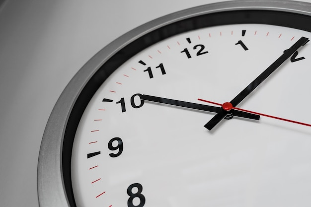 Closeup clock on the wall for business hours on time concept. Premium Photo