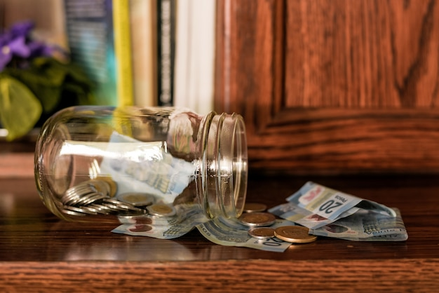 Primo piano di monete in un barattolo sul tavolo con pesos sotto le luci Foto Gratuite
