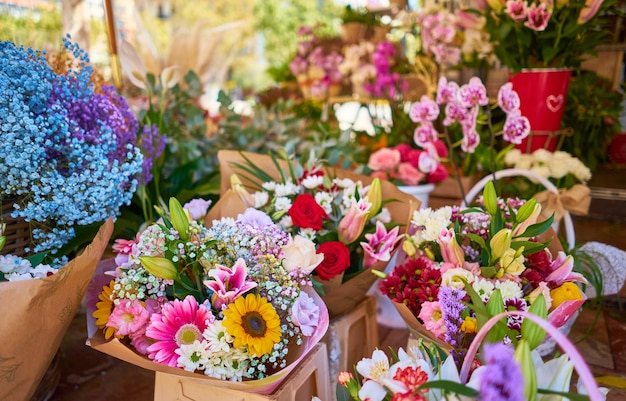 Closeup of colorful flower bouquets in containers at an outdoor shop Free Photo