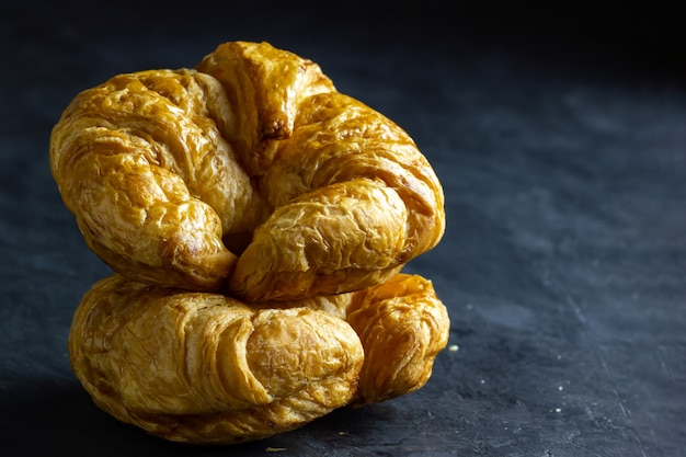 Closeup croissant on table in dark background. copy space for text. Premium Photo