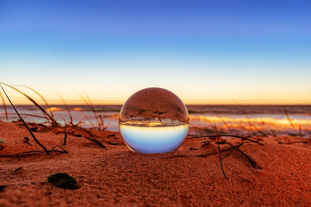 Closeup of a crystal ball on the beach with the surroundings reflecting on it Free Photo