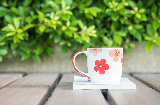 Closeup cup of coffee on white book on table in the garden background Premium Photo