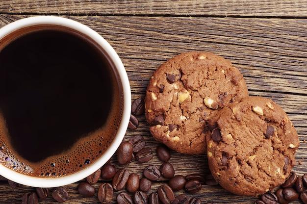 Крупным планом чашка горячего кофе и шоколадного печенья с орехами Premium Фотографии