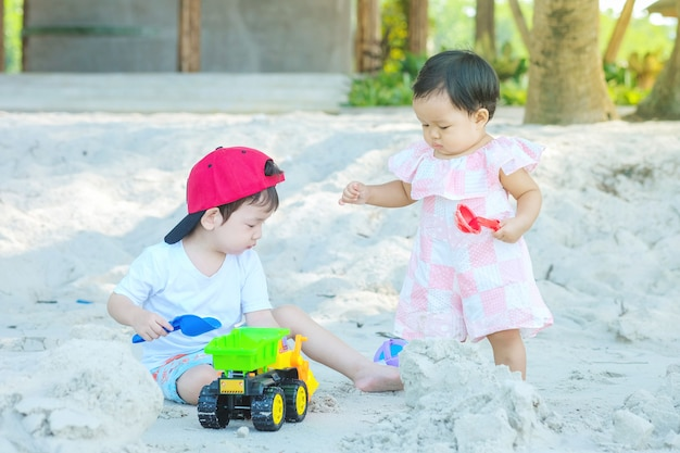 Closeup cute asian boy and girl play with sand and toy on beach textured background Premium Photo