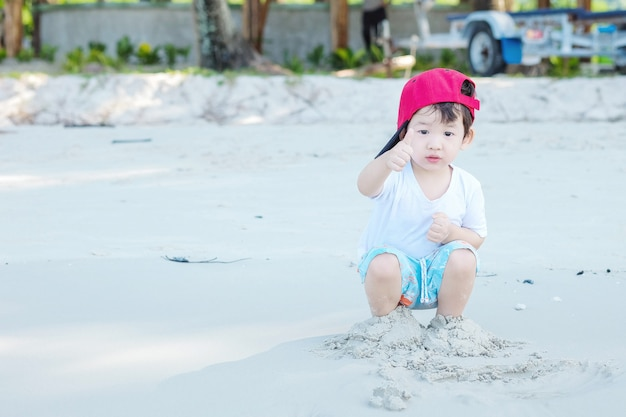Closeup cute asian kid play with sand on beach textured background Premium Photo
