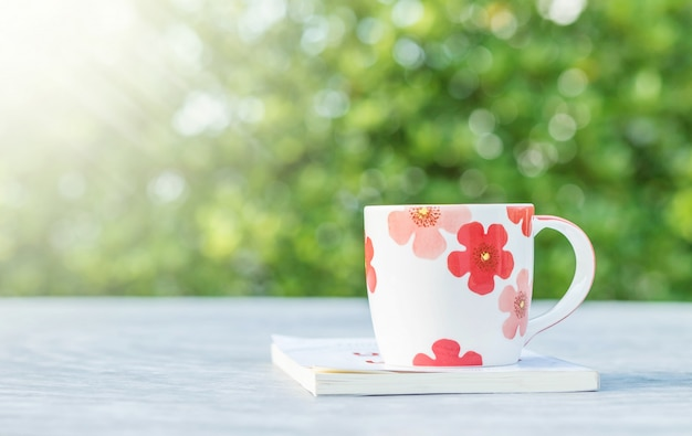 Closeup cute cup of coffee white book on blurred concrete desk and garden view in the morning textured background Premium Photo