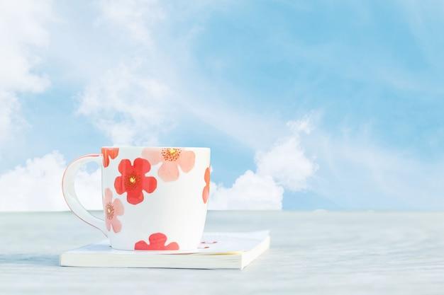 Closeup cute cup white book on desk with beautiful blue sky background Premium Photo