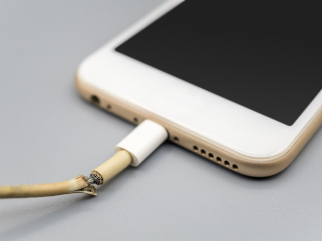 Closeup the damaged smartphone charger cable Premium Photo