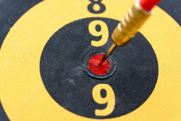 Closeup dart hitting on bullseye target Free Photo