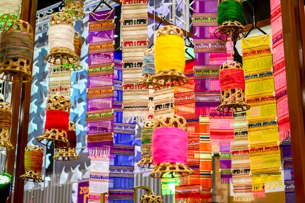 Closeup decorative wicker lantern and lanna fabric long flags (tung) hang on hotel lobby ceiling and blurry background. Premium Photo