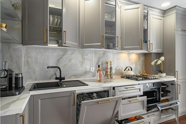 Крупные детали серо-белой современной классической кухни, выполненной в современном стиле, все мебельные дверцы и ящики открыты Premium Фотографии