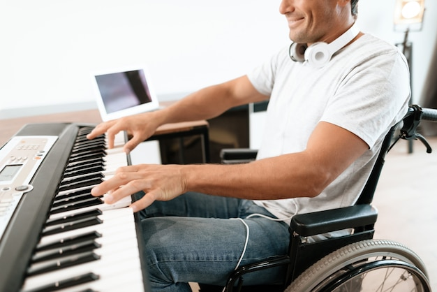Closeup of disabled male hands plays synthesizer. Premium Photo