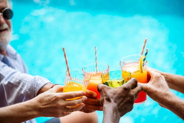 Closeup of diverse hands clinking drinks together Premium Photo