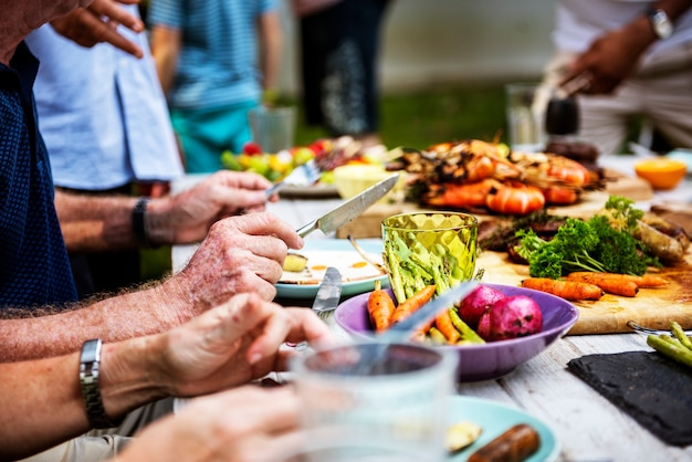 Closeup of diverse people enjoying barbecue party together Free Photo