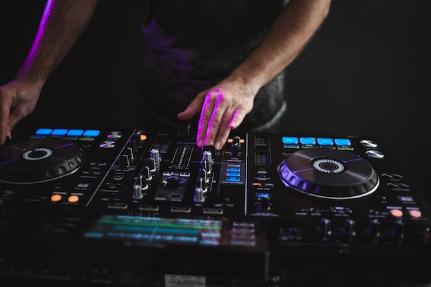 Closeup of a dj working under the colorful lights in a studio Free Photo