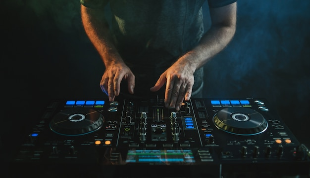 Closeup of a dj working under the lights Free Photo