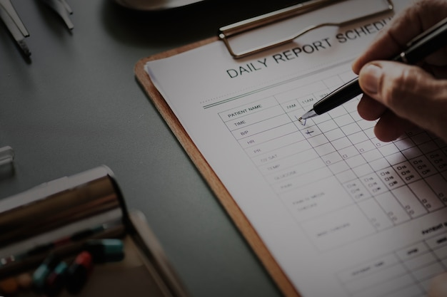 Closeup of doctor checking patient daily report checklist Free Photo