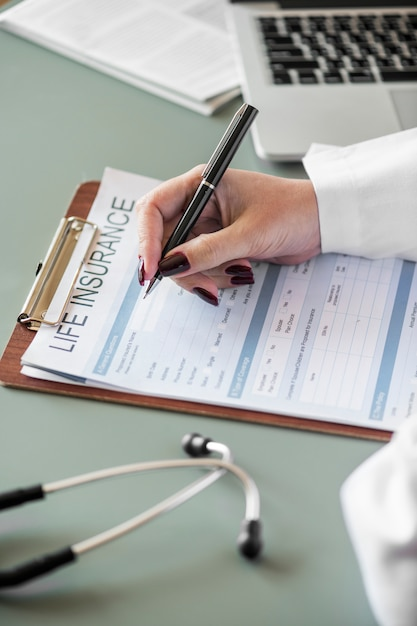 Closeup of doctor filling life insurance form Free Photo