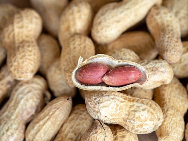 Closeup dried peanuts in shells on peanuts background on wooden table Premium Photo