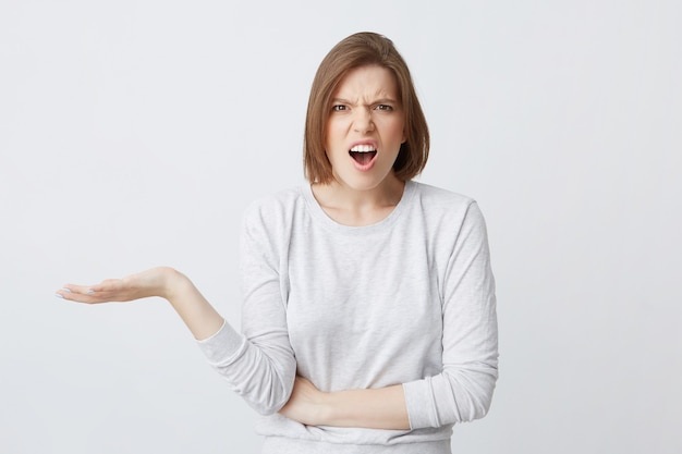 Closeup of embarrassed displeased young woman in longsleeve looks confused Free Photo
